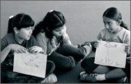 Three girls sitting and showing their drawings
